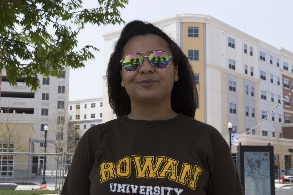 Melanie wearing metallic sunglasses standing on Rowan Blvd.
