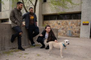 Monica and her friends stand outside of Robinson Hall, petting a dog.
