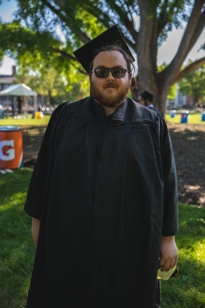Johnathan Puglise wears his black glasses as he poses in his black cap and gown for graduation.