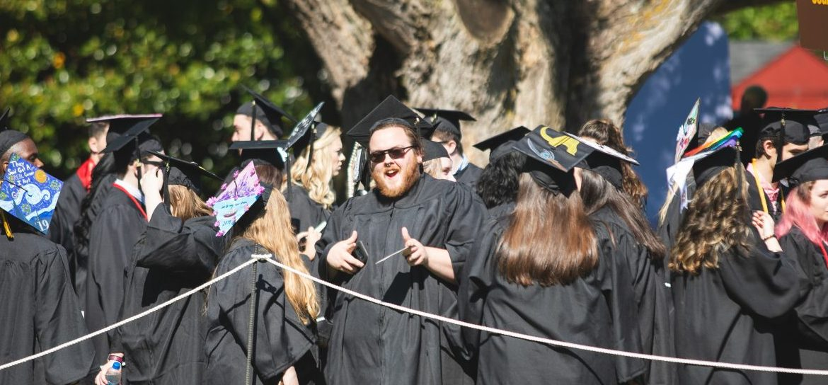 Johnathan Puglise smiles at the camera while being surrounded by other recent graduates in their black cap and gowns.