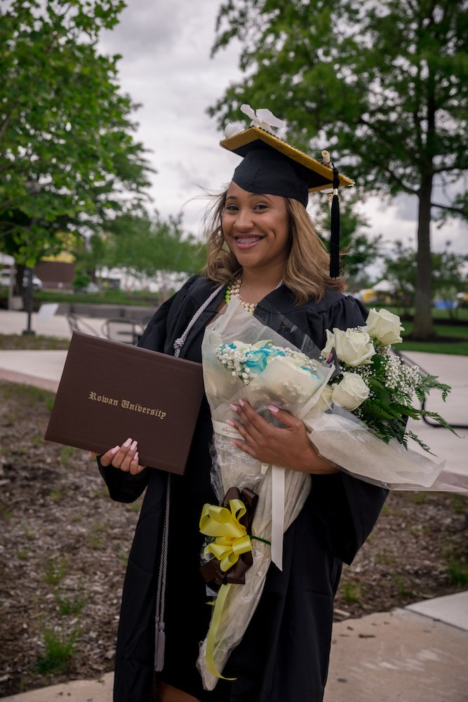 Cieani in her graduation gown holding flowers in her hand.