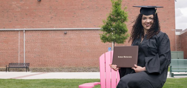 Eduarda in her graduation gown sitting on a pink wooden chair
