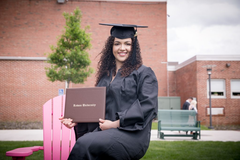 Eduarda in her cap and gown sitting on a pink chair