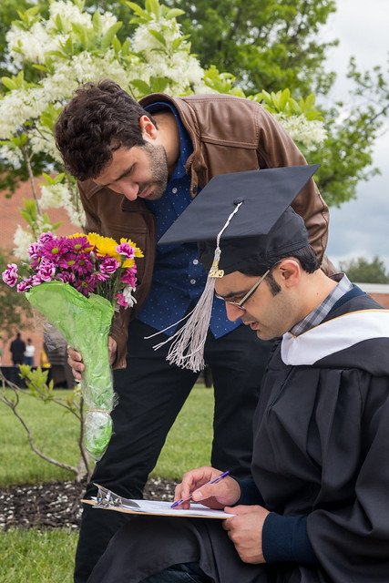 Ahmad Kindawi jots notes after graduation with family looking on holding a bouquet of flowers at Rowan University
