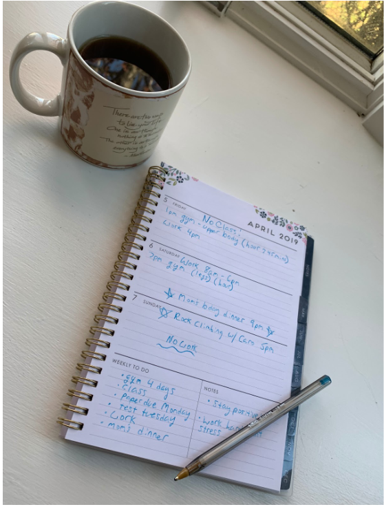 An opened planner with a cup of coffee next to it