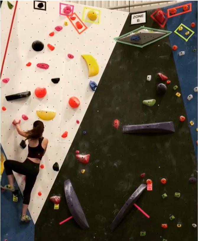 A woman going up a rock-climbing wall