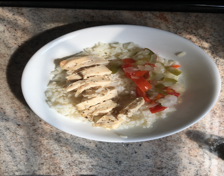 A plate of chicken over rice with vegetables