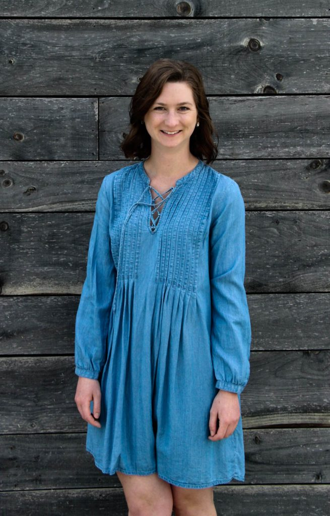 Amanda wearing a blue dress standing in front of a wooden background
