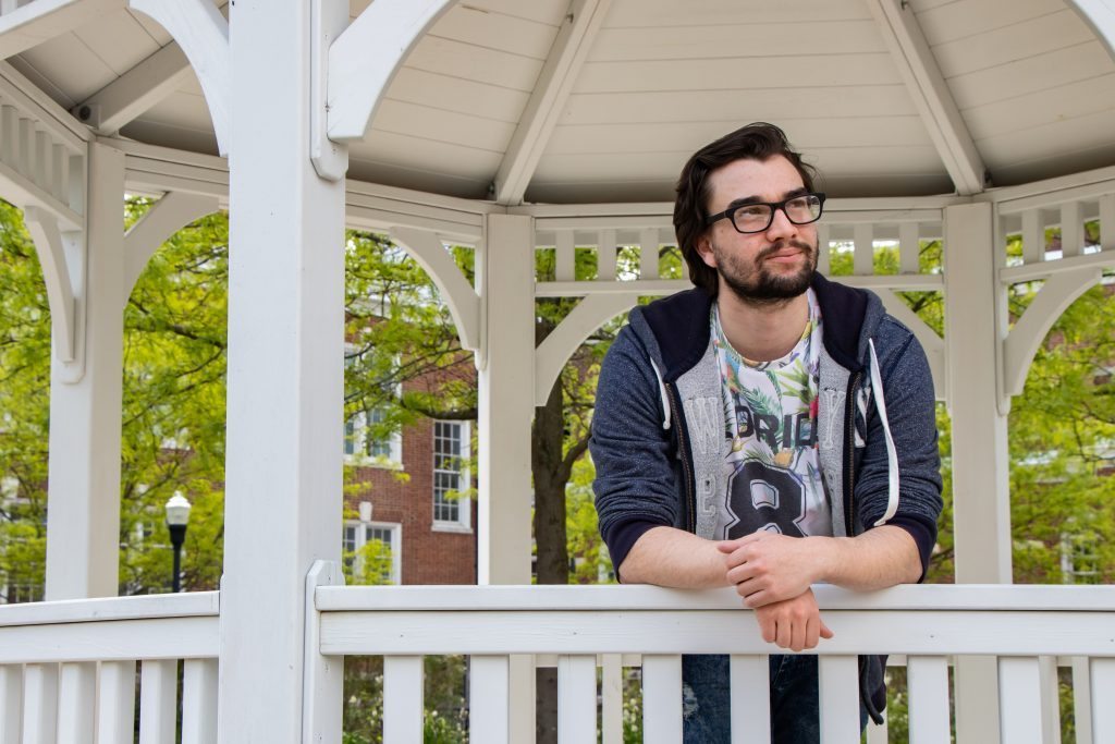 Young male student inside a white gazebo leaning against the railing