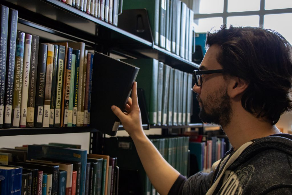 Young male student grabbing a library book off the shelf