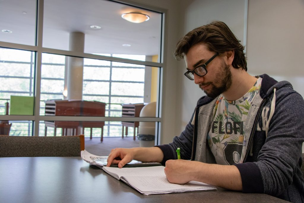 Young male student sitting at a table studying and writing notes