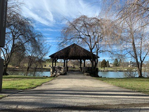 Gazebo with stone path leading to it and a lake with trees in the background