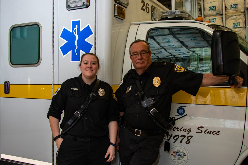 Two EMS team members standing together in from an EMS transport vehicle