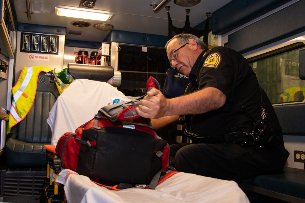 EMS employee reviewing medical supplies inside the back of an EMS transport vehicle
