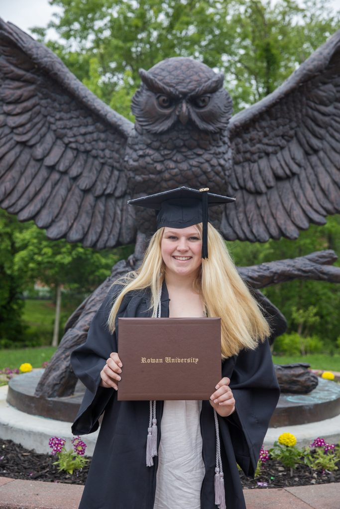 Cheyenne stands in front of owl statue at Rowan University, wearing an open graduation gown and holding a brown diploma holder