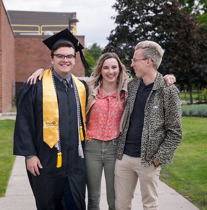 Christian stands with two friends, wearing his graduation gown from Rowan University