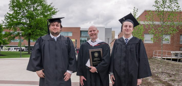 history grads pose with professor, wearing graduation gowns at Rowan University
