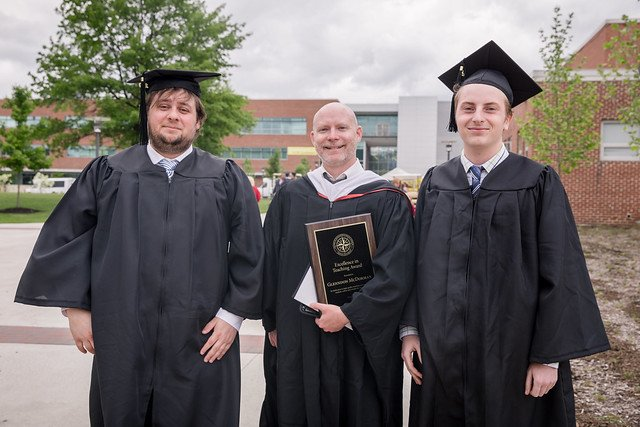 history grads pose with professor after graduation at Rowan University