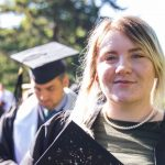 Kelsey, in her graduation gown, holding her decorated cap