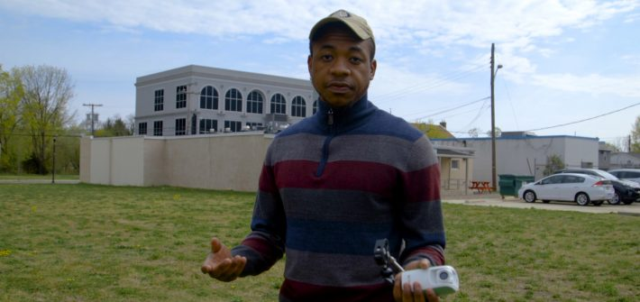Rashaun Brown stands outside in the vacant lot.