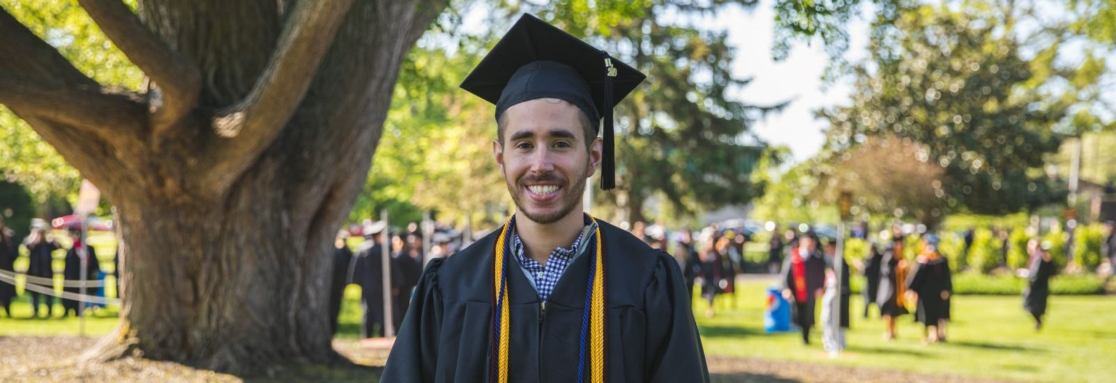 Alex, wearing his graduation cap and gown, standing on the Bunce Green.
