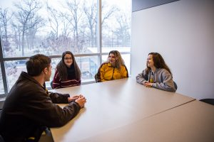Rowan students talking in a meeting room.