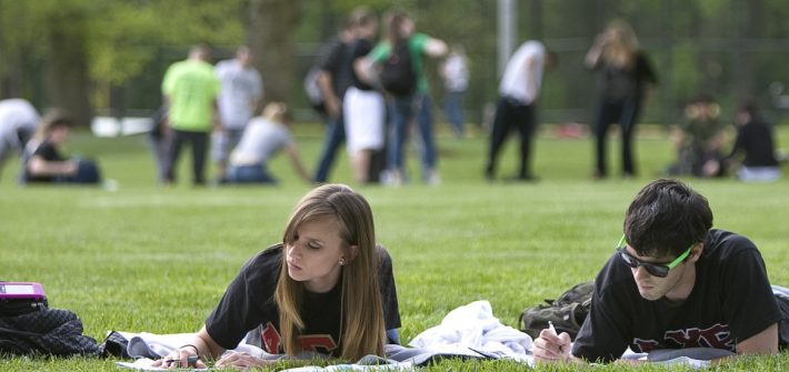 Students studying and playing on a field