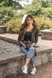 Iridian sits on stone ledge at Rowan University, legs cross while holding a camera for Rowan Blog