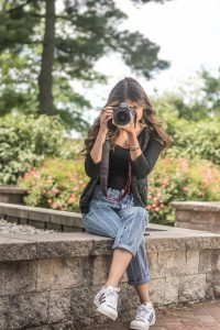 Iridian sits on a rock wall at Rowan University, holding a camera to take a picture
