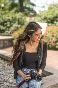 Iridian laughs, head turned to the side, at Rowan University