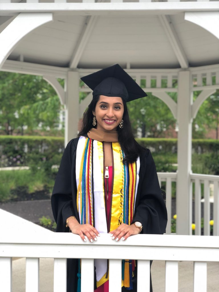 Young lady in a graduation gown with a dozen cords posing inside a white gazebo
