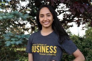 Young lady with a grey shirt that references Rowan University's Roher College of Business standing in the foreground with trees in the background