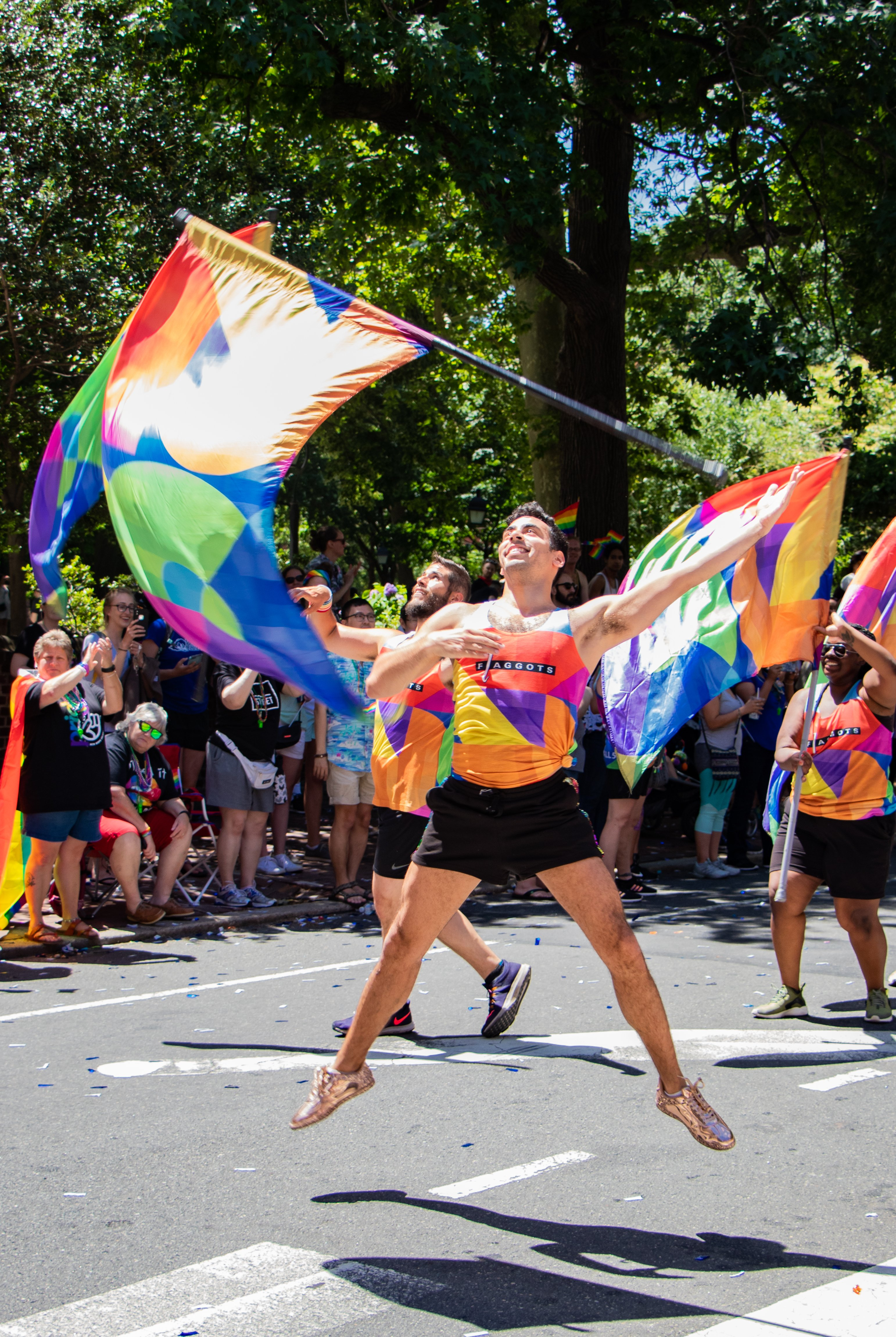 Man dressed in a rainbow outfit jumping mid-air trowing a rainbow flag up