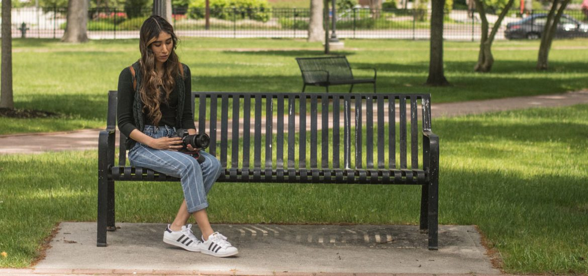 Iridian Gonzalez sits on a bench outside of Bunce Hall