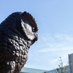 A close up of the owl statue under blue skies