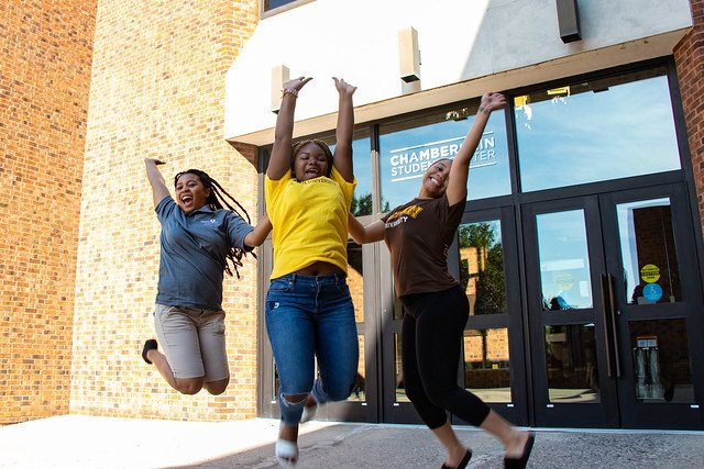 Dyone Payne jumps for joy with two friends outside the Student Center