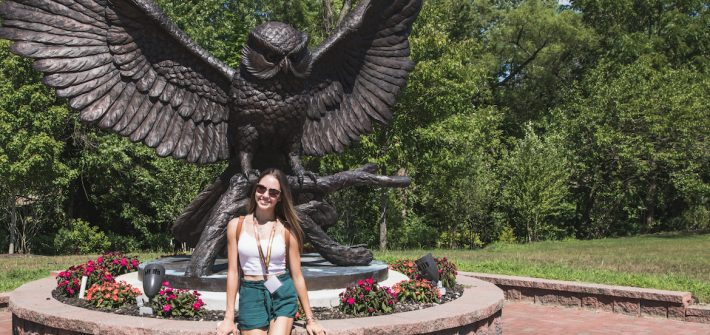Ariana poses in front of the Rowan Owl statue.