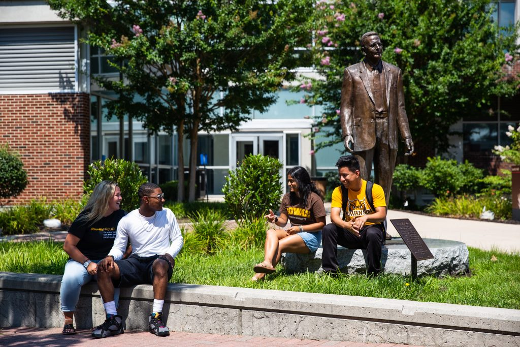 four students sit by the Henry Rowan statue chatting