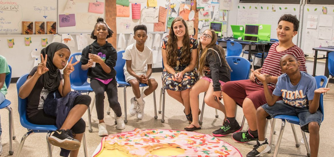 Kasey DiSessa of Rowan University sits in the middle of a row of middle school students she teaches