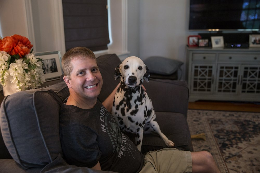 Steve and Lola the Dalmatian sitting on a grey couch.
