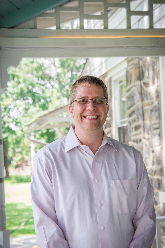 Steve McKeon posing for a portrait photo on his porch.