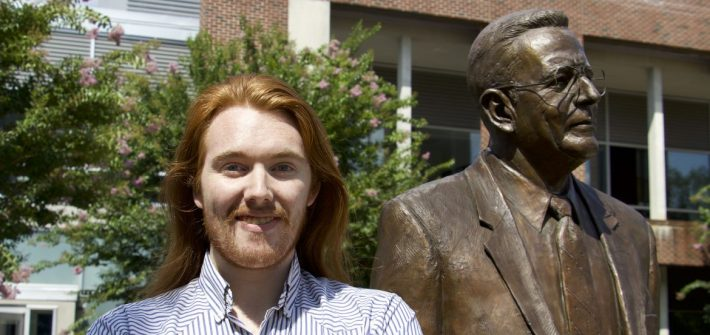 Rowan Music Performance major Jesse Panico next to the Henry Rowan statue