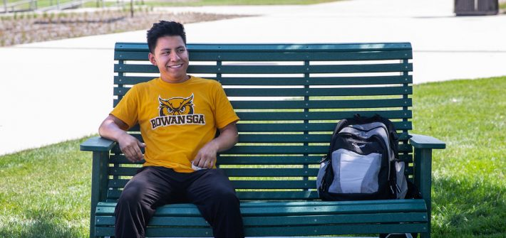 Alexis Benitez smiles, sits on a green bench with his bookbag by his side