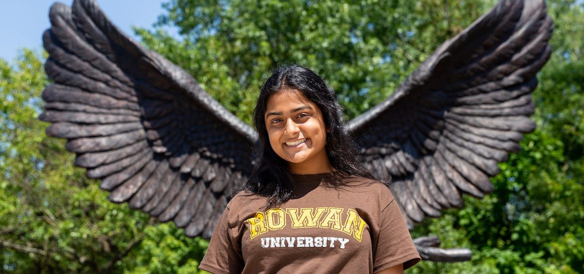 Krishna stands at Rowan University posed with the owl mascot's wings behind her