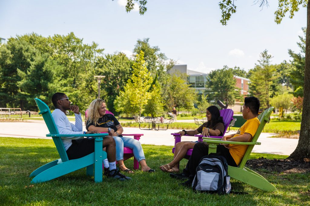 Silas sits with three friends on brightly colored Adirondack chairs on a lawn at Rowan University