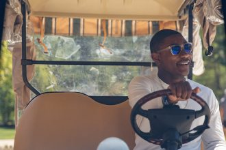 Silas sits in the driver's seat of a Rowan golf cart with one hand on the wheel, looking off camera