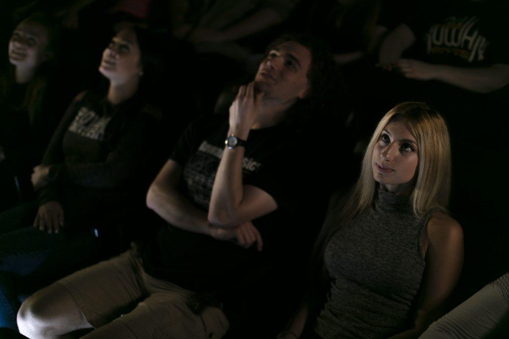 a row of student sit at the Rowan University planetarium, looking up at a presentation