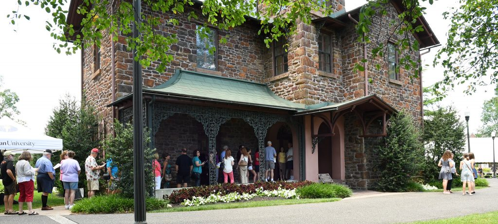 Line of people wait to enter the historic brick Hollybush Mansion at Rowan University
