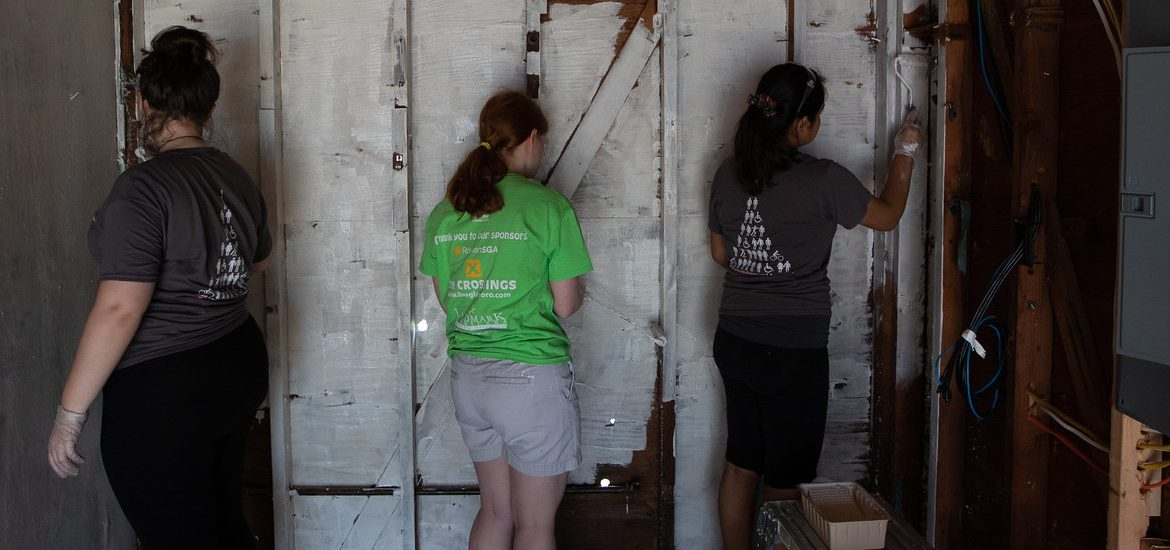 First-Year Volunteer Connection student leader Rose Dickmann (center, in green) helps out at the St. Bernard's disaster relief project.