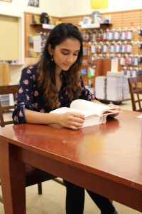 Molecular and cellular biology major Amaal Khan sitting and reading a book at Rowan Barnes and Noble